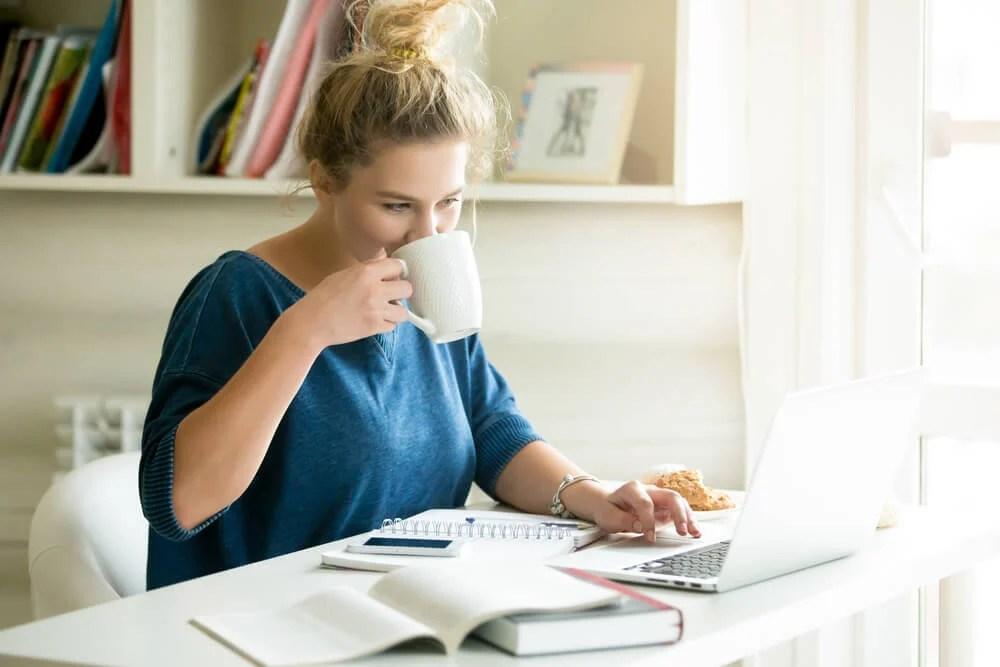 mulher tomando café enquanto trabalha em home office