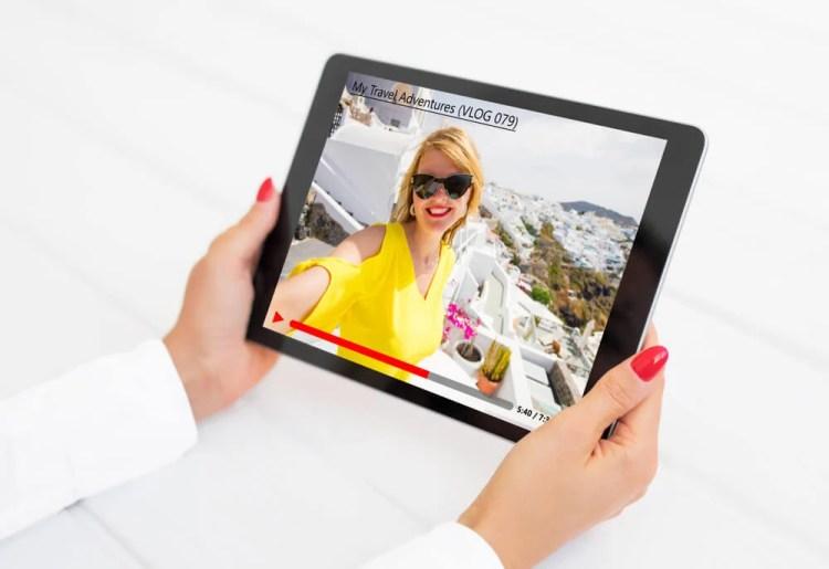 maos femininas segurando tablet com vlog de viagem da plataforma youtube em tela