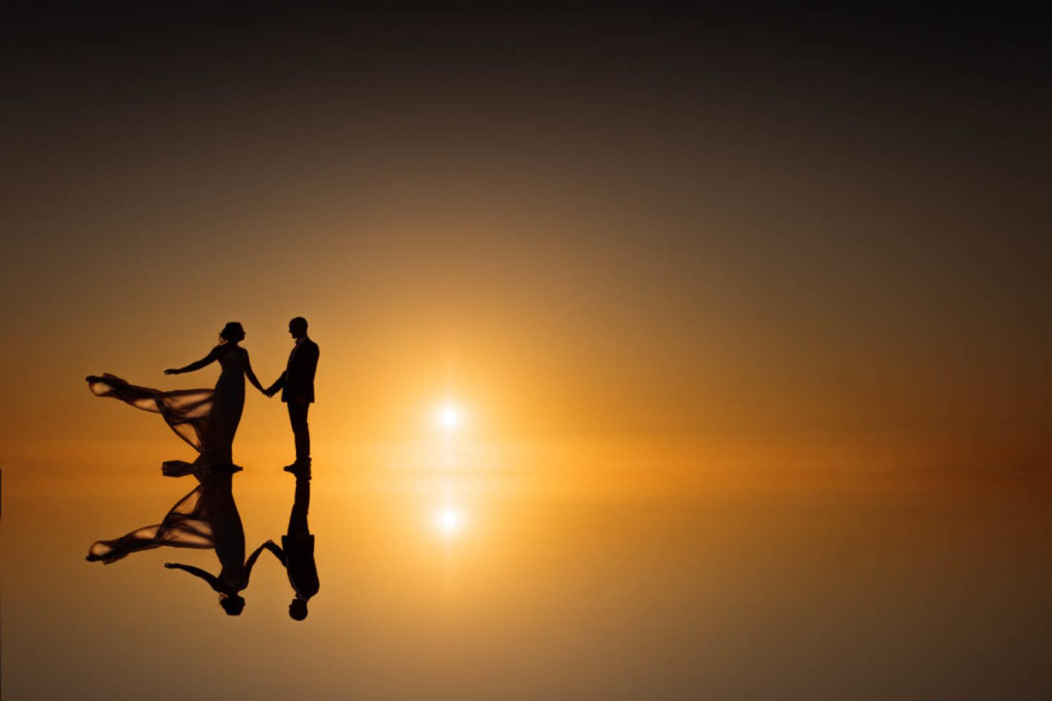 Lancashire Wedding Photographer - Golden sunset with Bride and Groom silhouttes which are reflected at Formby Beach and Squirrel Park