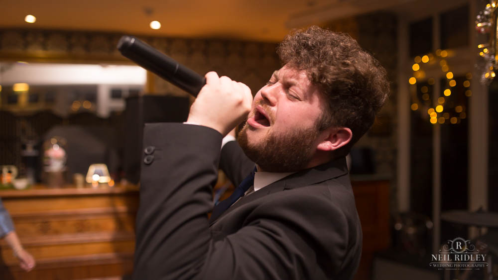 Lead singer of Boombox Party Band holding microphone to his mouth at Broadoaks Country Hotel Lake District