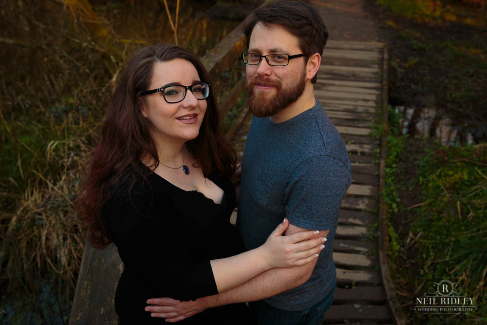 Lancashire Pre Wedding Shoot at Scorton Lake, a young couple embrace on a wooden walkway