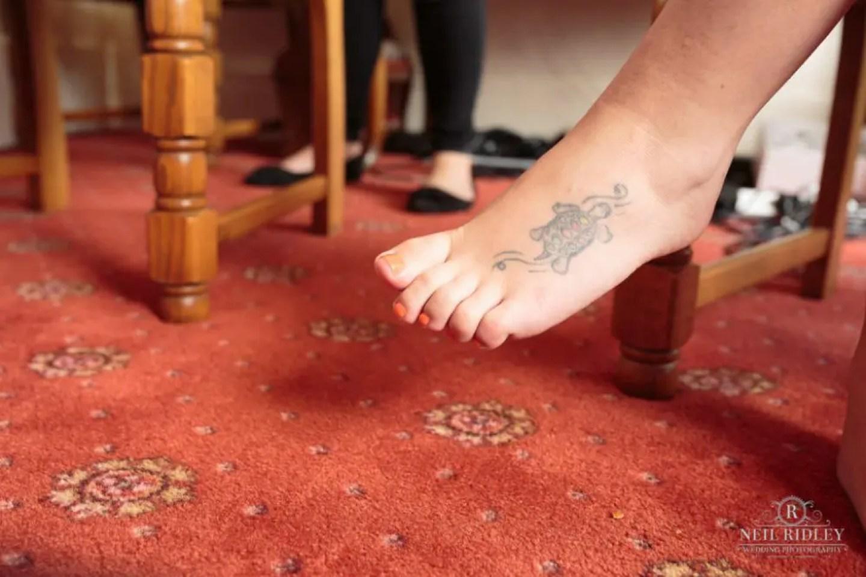 Tattoo of turtle on Bride's foot.