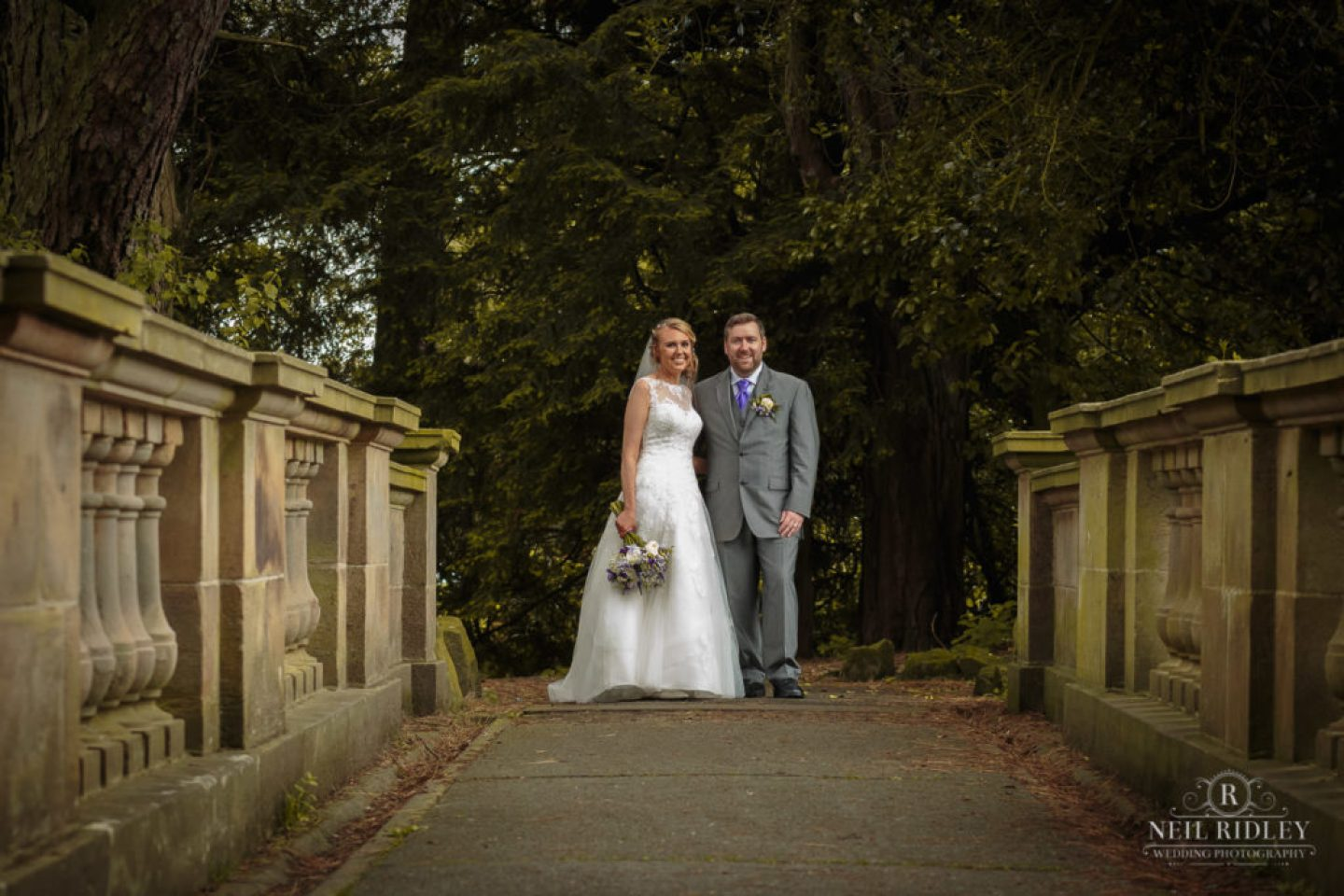 Lancaster Wedding Photographer - Bride and Groom stand on bridge at Williamson Park Lancaster