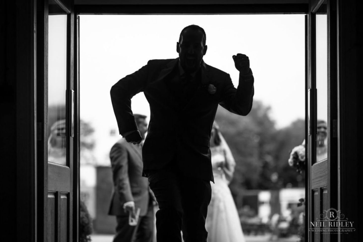 Lancaster Wedding Photographer - Balck and white image silhouette of Best Man entering Lancaster Brewery