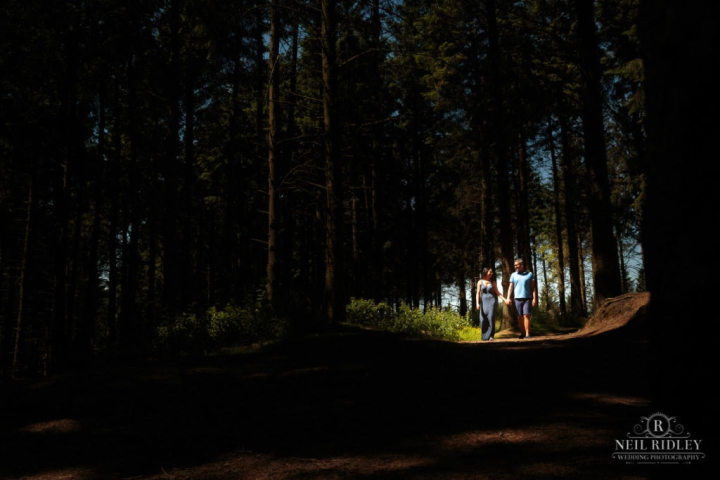 Engagement Shoot Couple walk through a pocket of light in the forest at Beacon Fell Lancashire