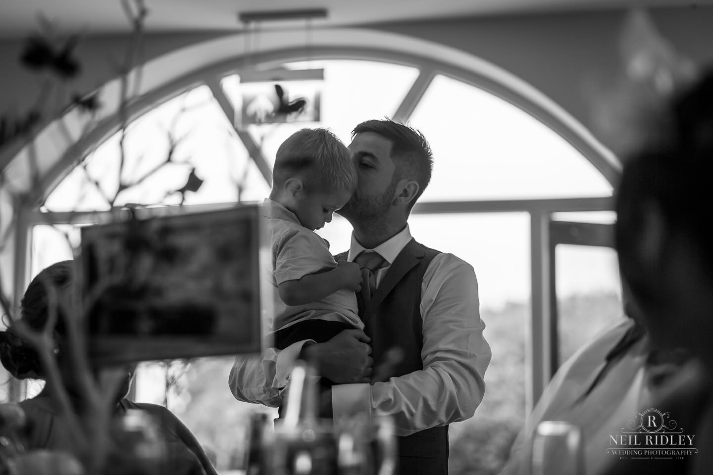 Father kisses child at The Mill at Conder Green