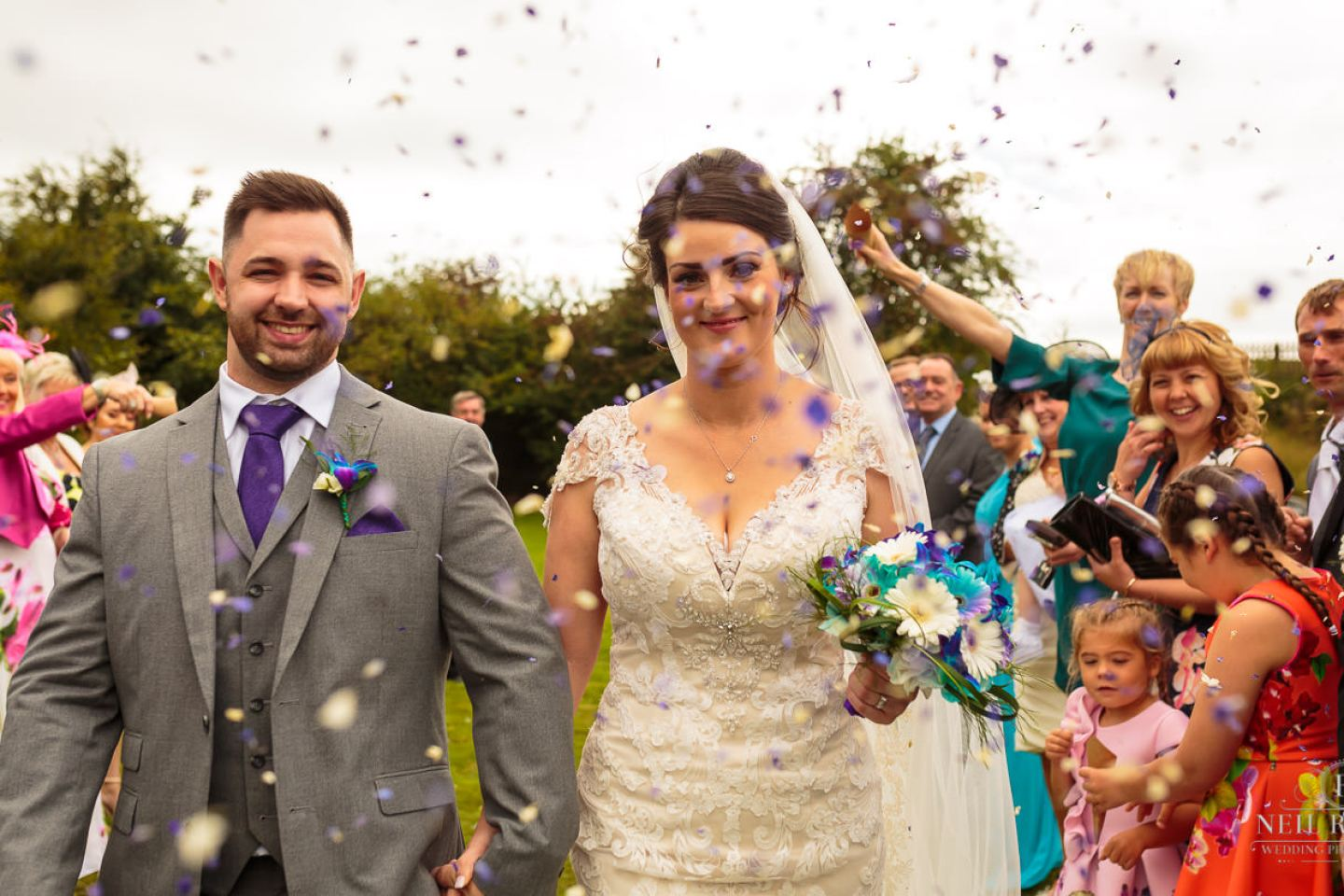 Bride and Groom walk through confetti at The Mill at Conder Green Lancashire Wedding Photographer