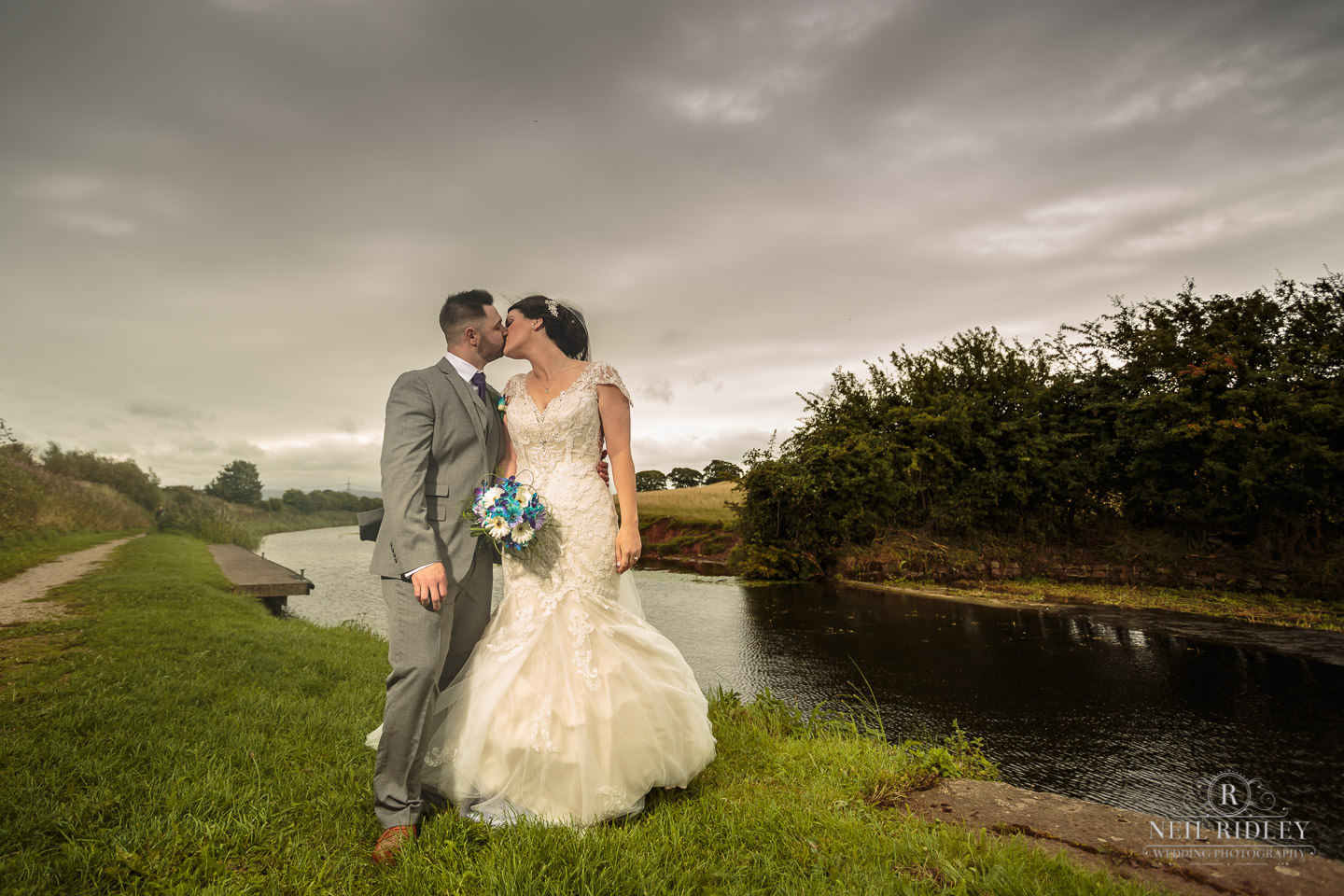 Bride and Groom stands next to Lancaster Canal and share a kiss at The Mill at Conder Green