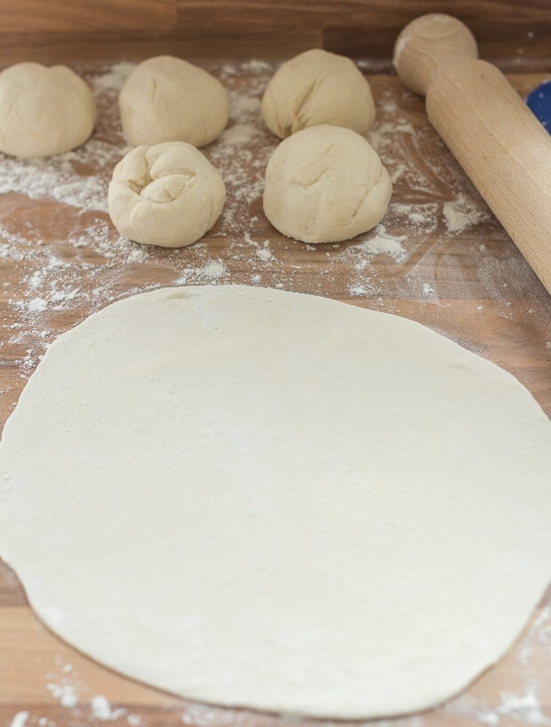 Roll out the home made naan bread dough to a circle shape.