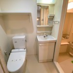 トイレ、洗面台。トイレ上部に棚あり。右手にユニットバス。