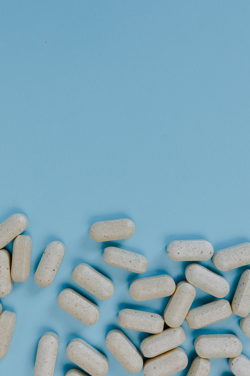 photo of white medication pill on teal surface