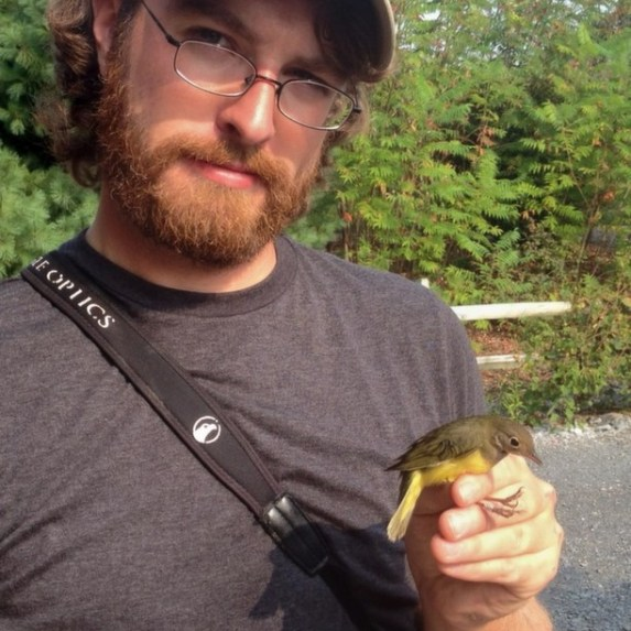 Alex Lamoreaux holding the Connecticut Warbler (Photo by Nate Fronk)