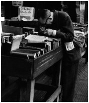| Fourth Ave, New York (man with lupe reading at Strand), 1959 |