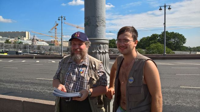 """Дежурные моста, волонтеры """"Солидарности"""", раздают доклады."""