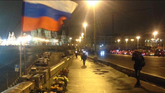 Молодой человек снимает мемориал с флагом для Дмитрия Гудкова, который регулярно выкладывает эти фотографии в своём твиттере.