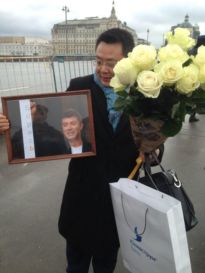 А вот китайский гражданин не только с цветами, но и с портретом!
