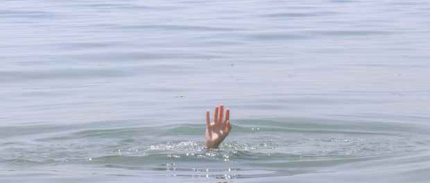 person s hand above water