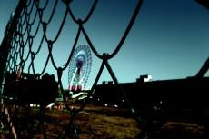 フェンス越しの観覧車と暗い空