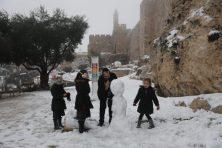 Jeruzsálem, 2021. február 18. Hóembert épít egy apa lányaival Jeruzsálem óvárosában 2021. február 18-án. MTI/EPA/Abir Szultan