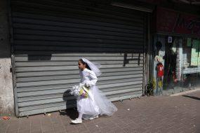 Menyasszonynak öltözött haredi kislány siet Bnei Brak egyik utcáján. Fotó: MTI/EPA/Abir Szultan