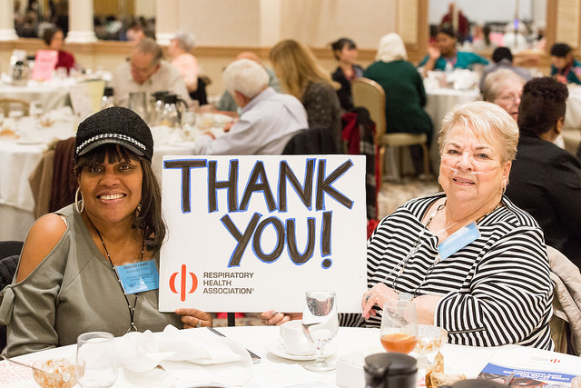 Two members at a Respiratory Health Association event holding up a thank you sign.
