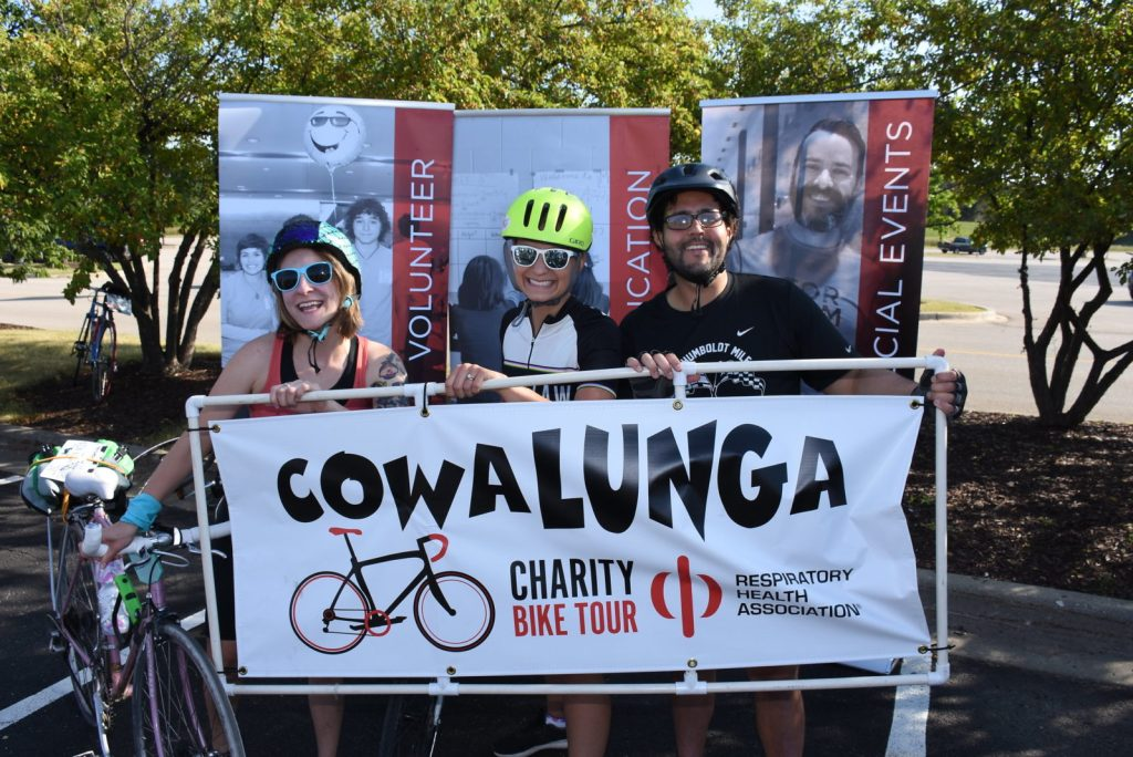 Three volunteers representing the Respiratory Health Associatoin stand with a sign for the Cowalunga Charity Bike Tour