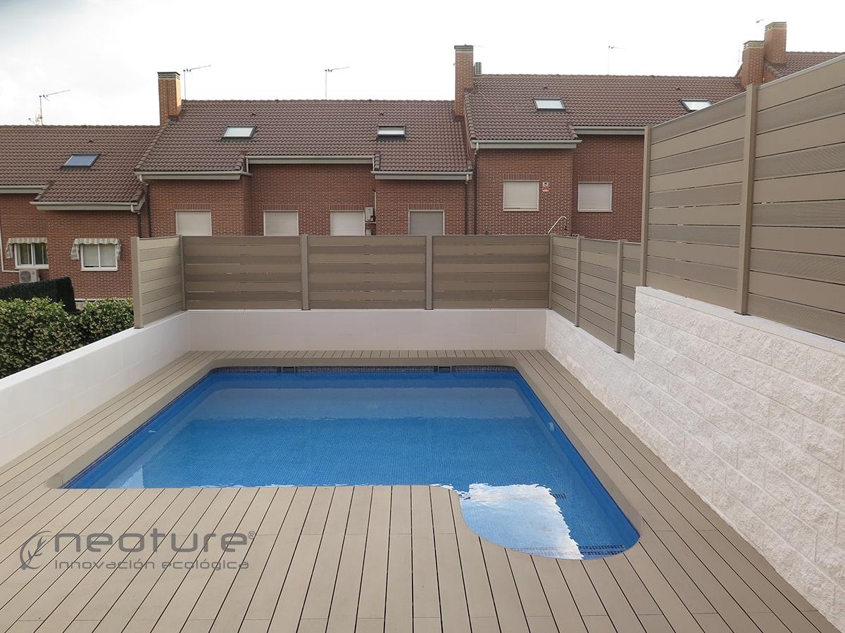 Vallado madera sintética exterior y tarima sintética alrededor de piscina.