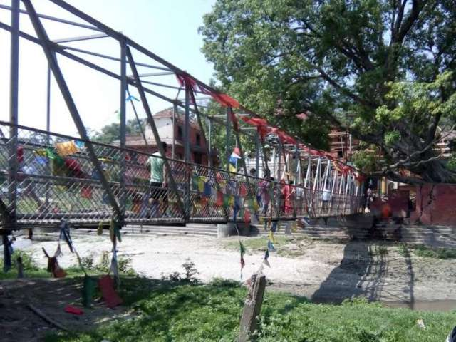 Guheshwori bridge covered with colorful prayer flags.