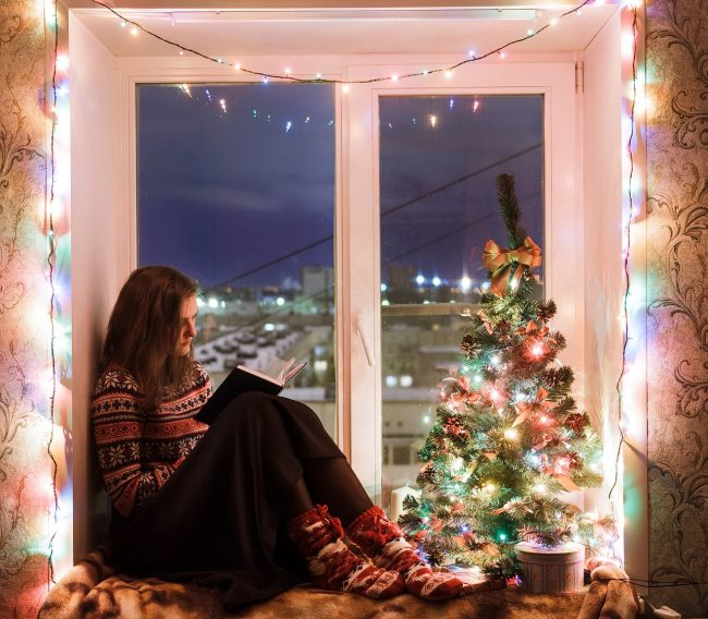 Holiday Reading Binge: Girl reading by the Christmas tree