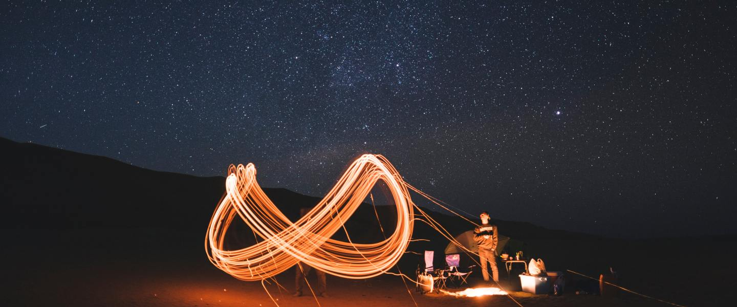 Man in starry campground, emitting the infinity sign