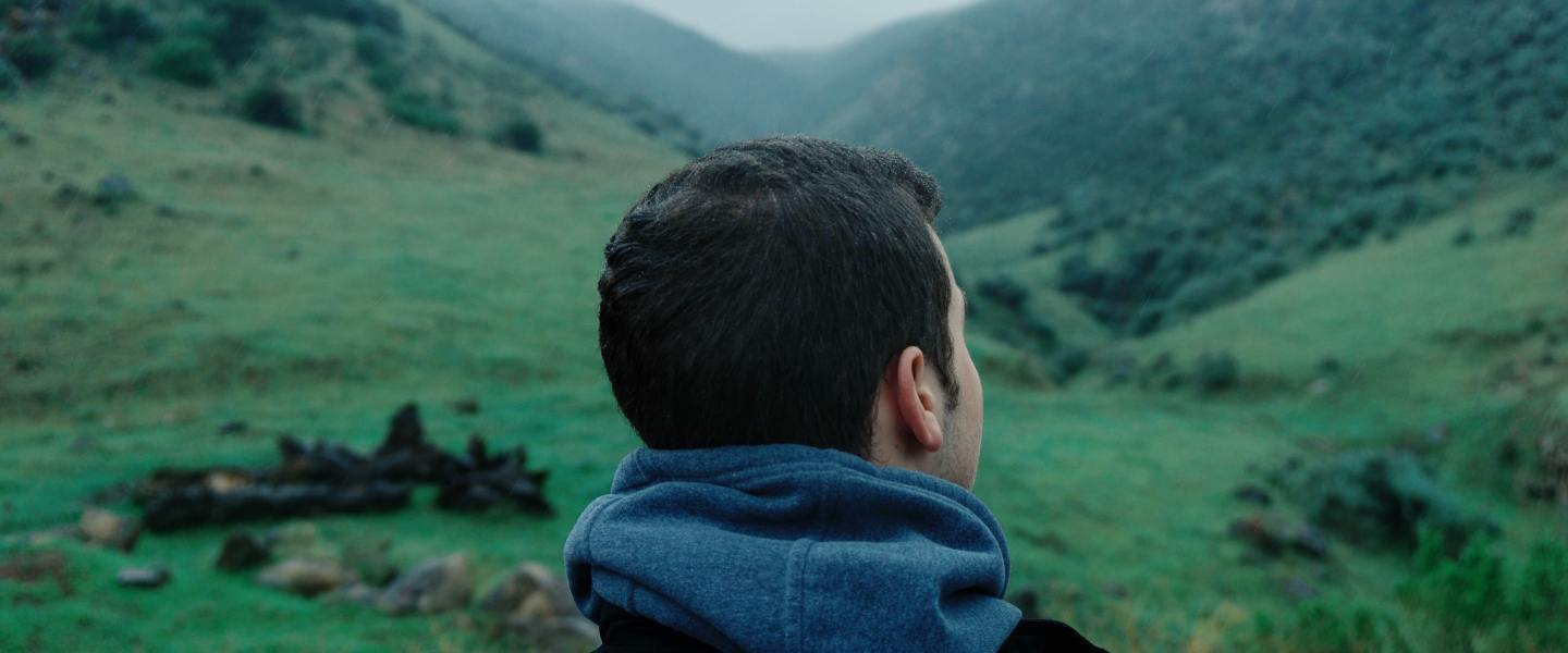 Man looking into the distance over hills