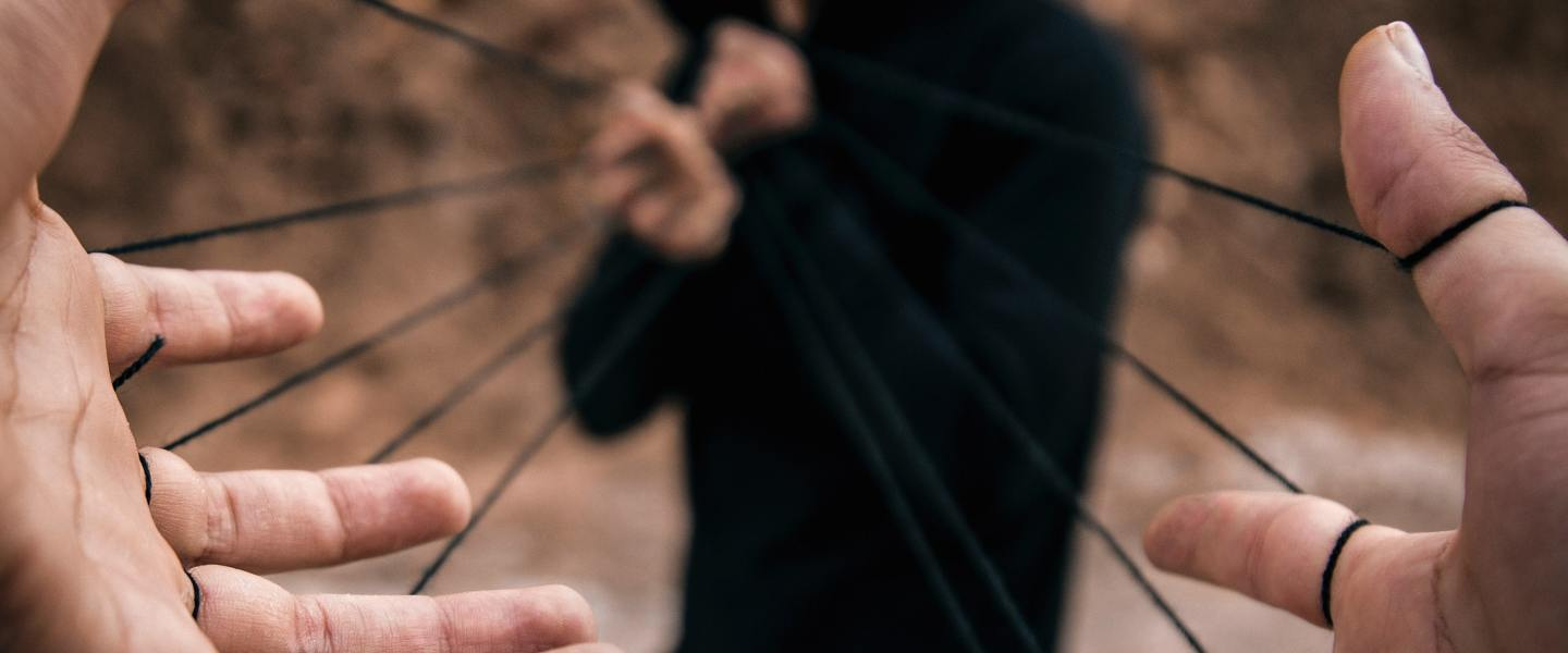 Man pulls back rubber band held by outstretched hands