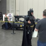 man in Batman costume with fans and Batmobile