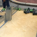 Children competing in a ball game using remote controlled robots.