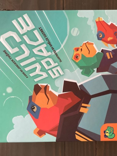 """A red bear, green monkey, and red lizard stand stoically in gray space uniforms, looking up to the stars. """"Wild Space"""" is the game title, angled up to the right in a techy font. Pandasaurus Games logo in the bottom left."""