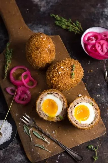 Scotch Eggs cut in half on a wooden cutting board with pickles