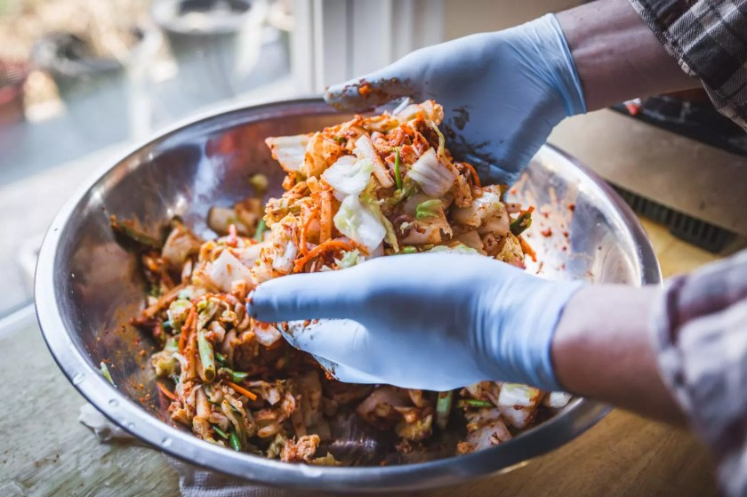 Gloved hands mixing kimchi in a big bowl