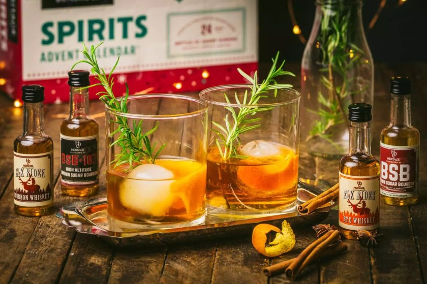 Two old-fashioned cocktails with miniature spirit bottles