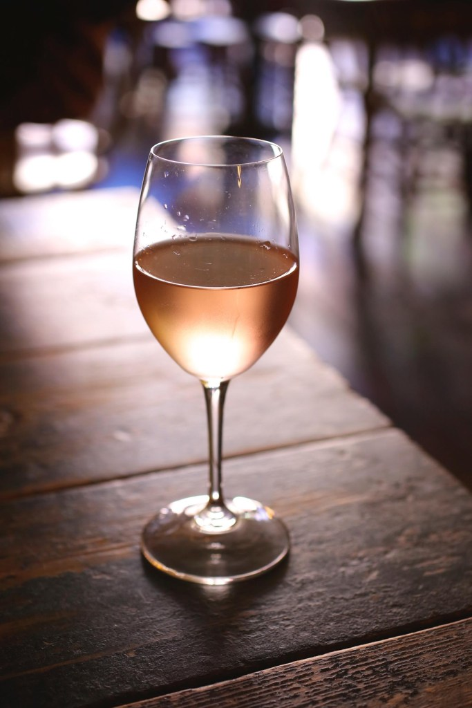 A glass of rose wine on a wooden table
