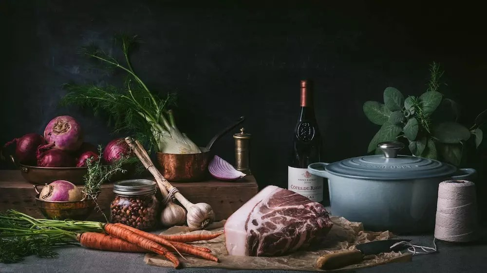 An arrangement of vegetables, a cut of beef, a bottle of wine and a Dutch Oven on a table