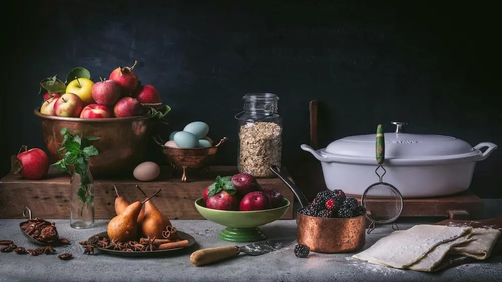 Fruit in bowls next to a bowl of oats and a low Dutch oven