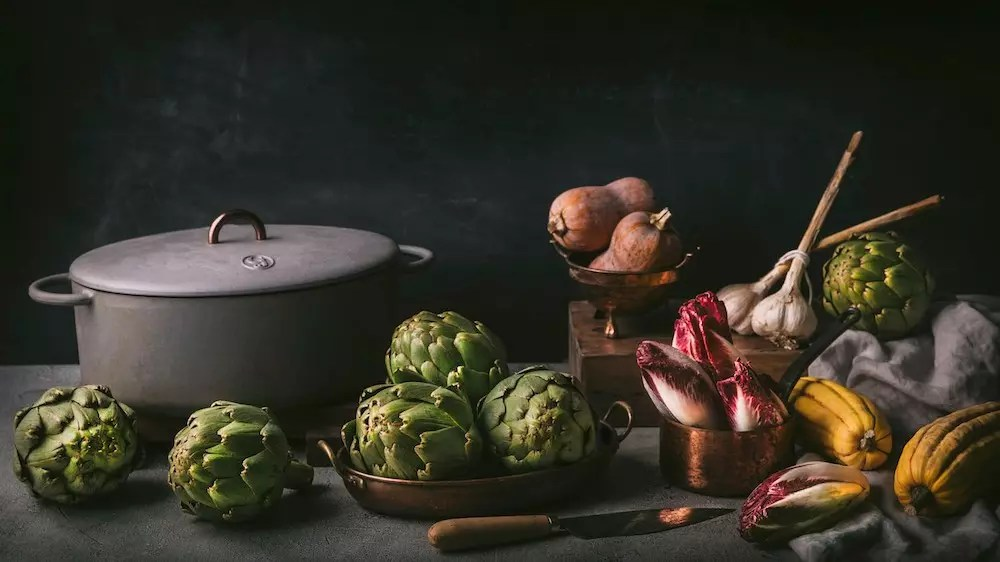 An arrangement of vegetables in pots and bowls next to a Dutch oven