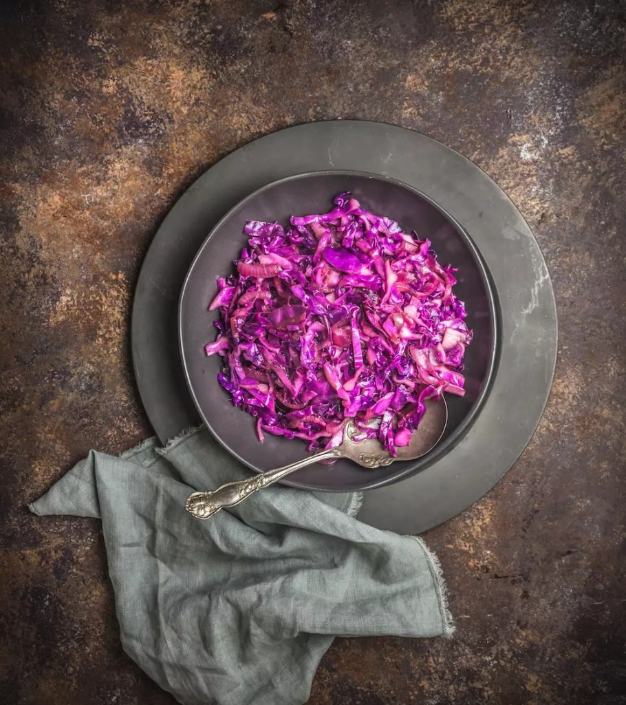 A pewter plate with braised red cabbage and a napkin