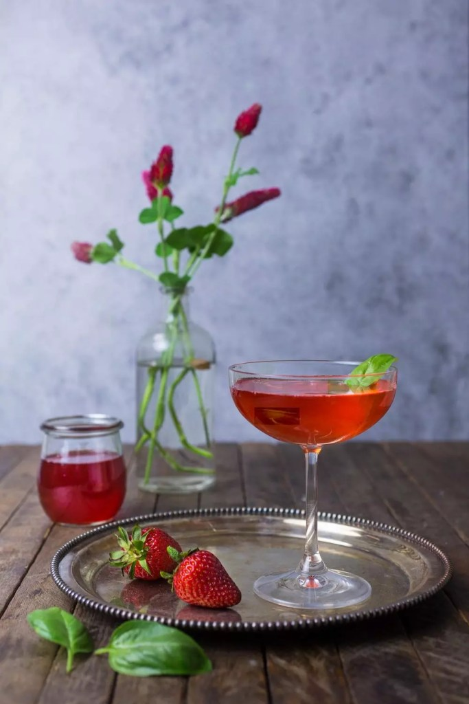 A bright red cocktail with strawberries on a plate and red flowers in a vase