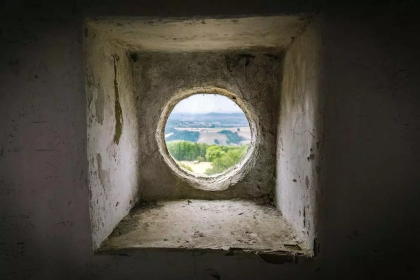 The view through a small round stone window onto a green English field