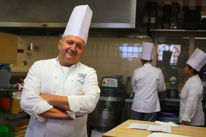 A chef wearing whites and a baker's hat folding his arms and smiling at the camera