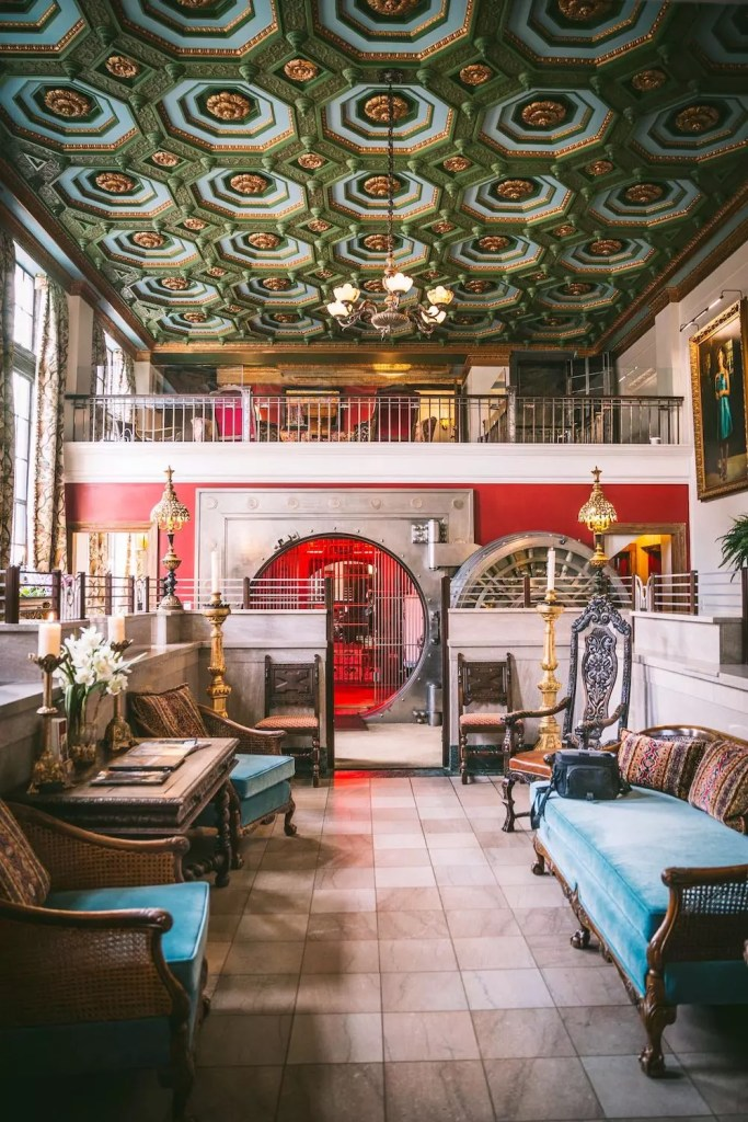 The grand interior of a hotel with ornate furniture and a converted bank vault