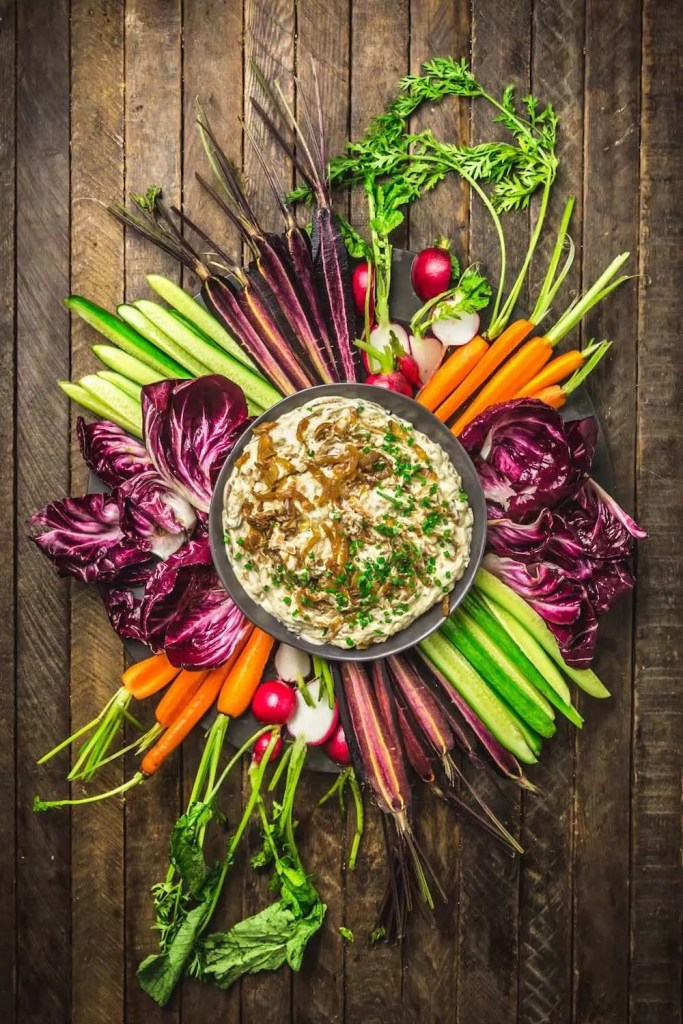 A dip surrounded by colorful cut veggies