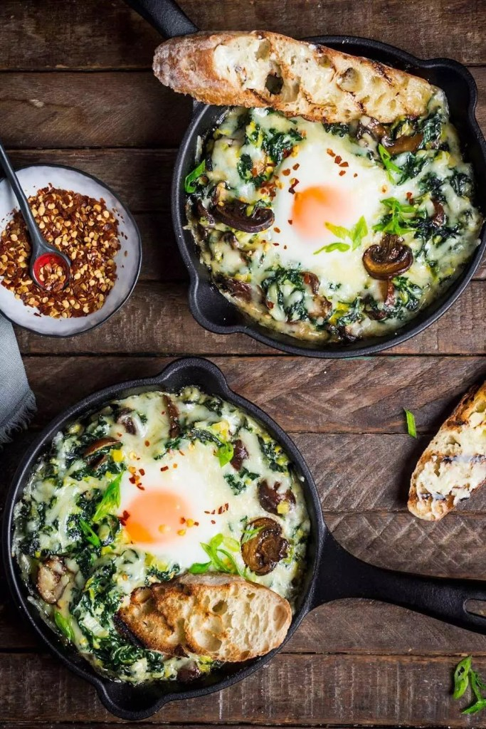 Baked eggs over greens in little cast iron skillets