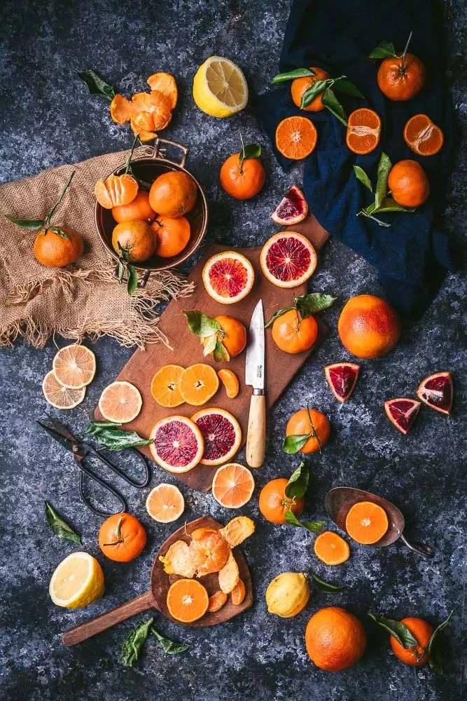 An assortment of whole and sliced blood oranges and mandarins